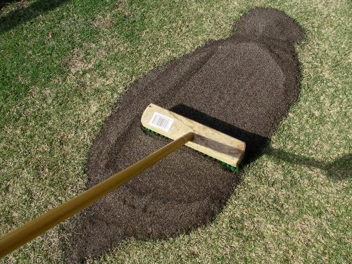 目土をトンボやブラシなどで薄く広げる