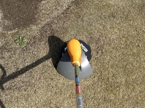 草刈機で芝生の不陸を削る